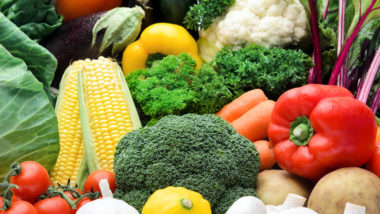 Close up of fresh raw organic vegetable produce, assortment of corn, peppers, broccoli, mushrooms, beets, cabbage, parsley, tomatoes, isolated on light background