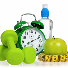 Green alarm clock, apple, bottle of water, measuring tape and dumbbells as concept of diet - isolated on white