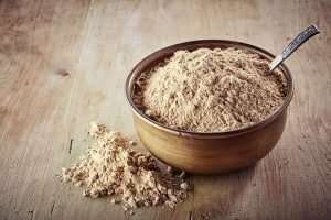 Bowl of maca powder on wooden background